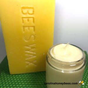 Homemade body butter with beeswax in a jar and large block of wax image.