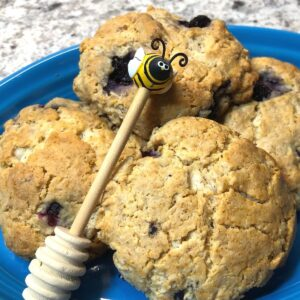 Homemade honey blueberry scones on a blue plate with bee dipper image.