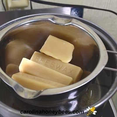 Melting bars of beeswas for diy lotion recipe in a double boiler image.