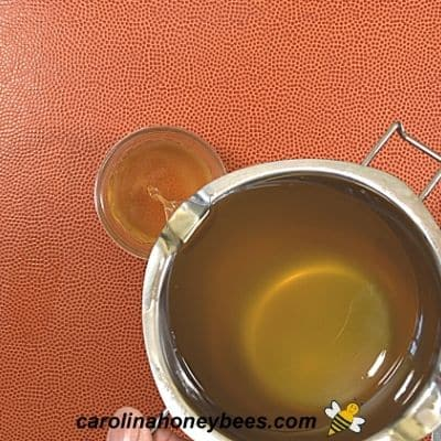 Pouring hot mixture of beeswax recipe into containers image.