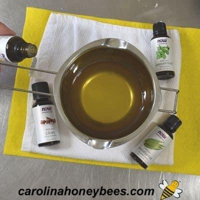 Adding essential oils to beeswax vapor rub recipe image.