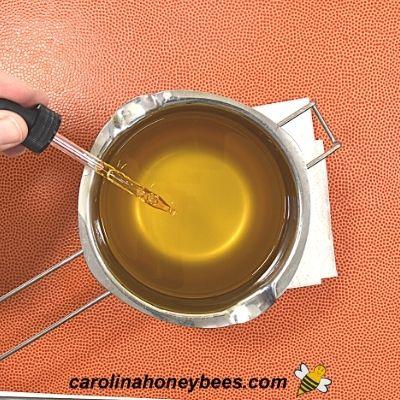 Adding drops of vitamin e oil to recipe for spoon oil image.