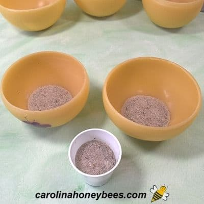 Sand poured in base of beeswax lanterns for insulation image.