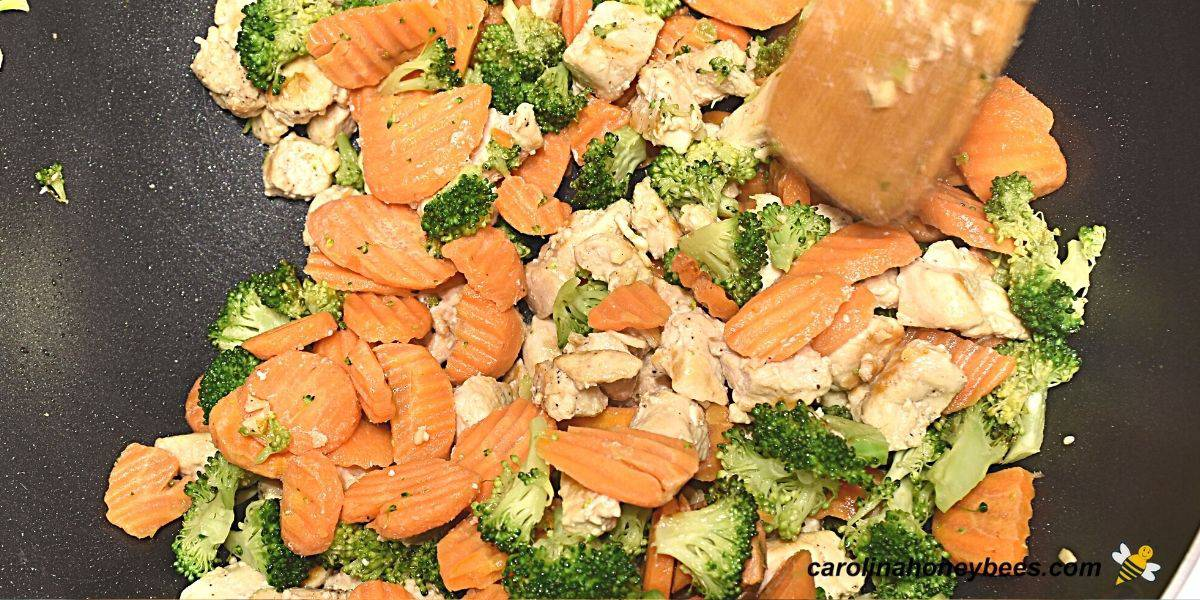 Pieces of chicken and vegetables in stir fry pot image.