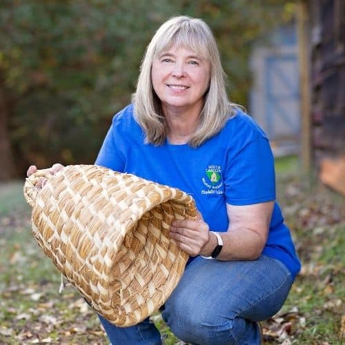 Charlotte Anderson beekeeper with a straw skep image.