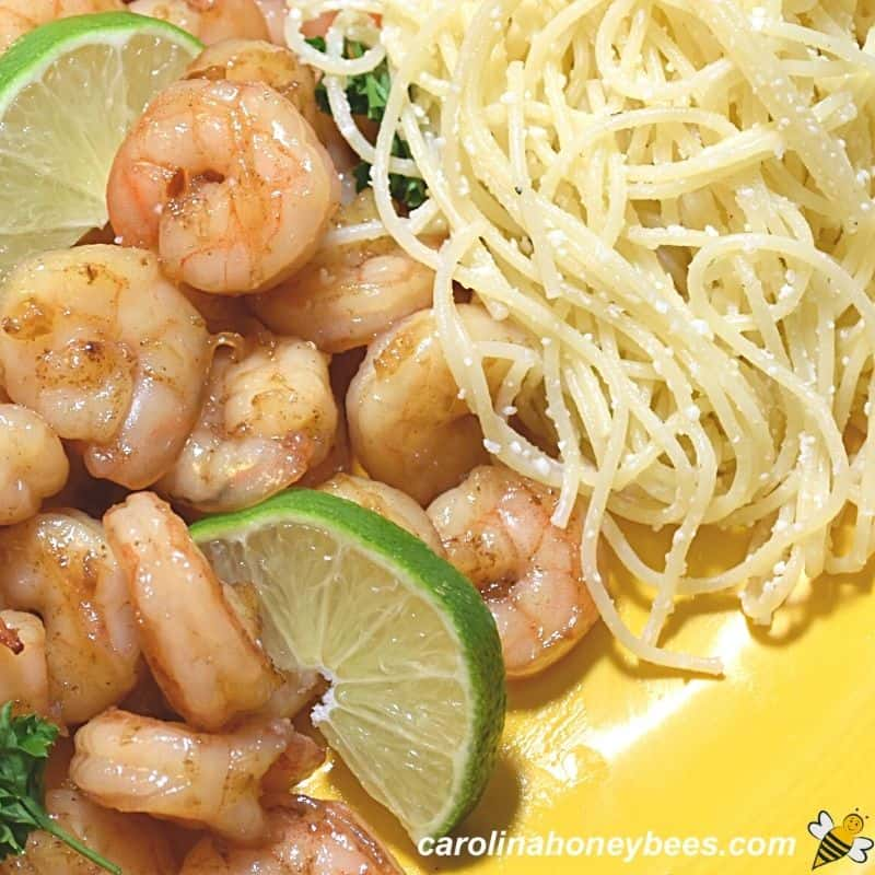 Shrimp stir fry with lime and pasta on plate image.