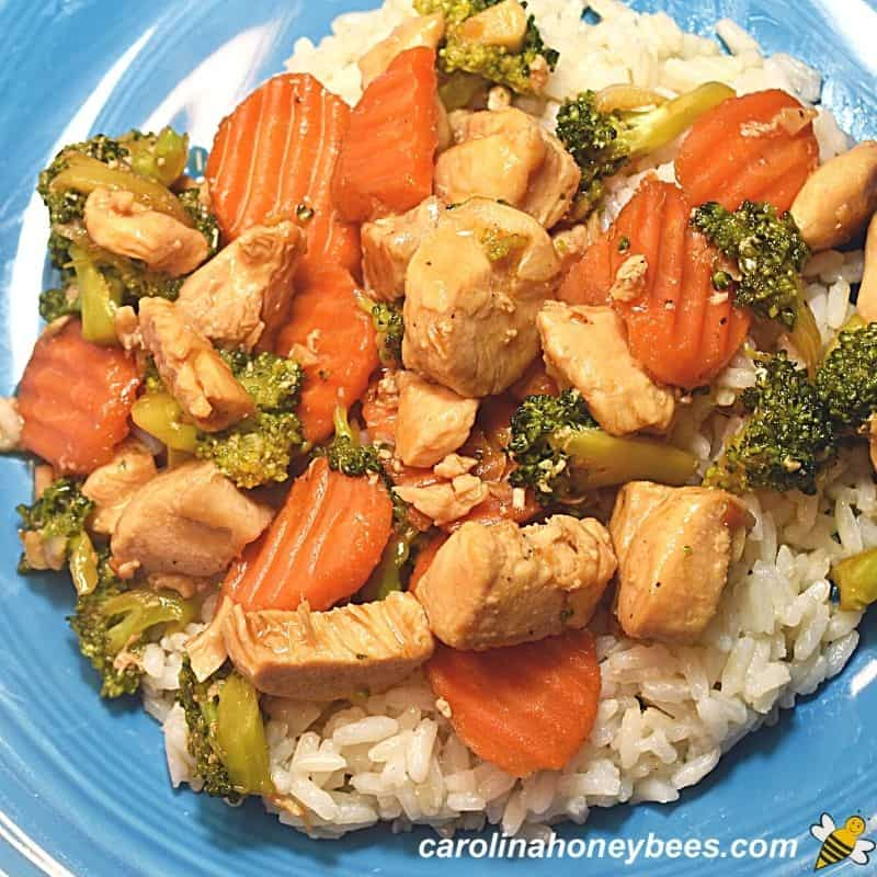 Honey chicken with vegetables stir fry over rice on plate image.