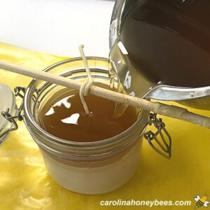 Filling candle jar with hot beeswax image.