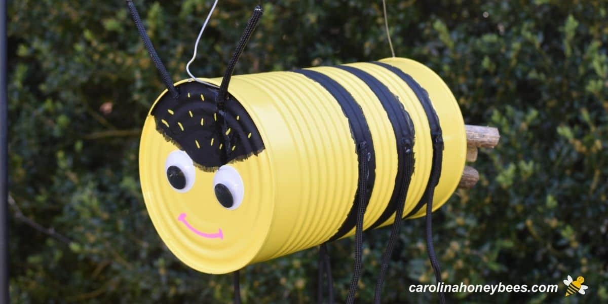 Tin can bee craft hanging in the garden image.