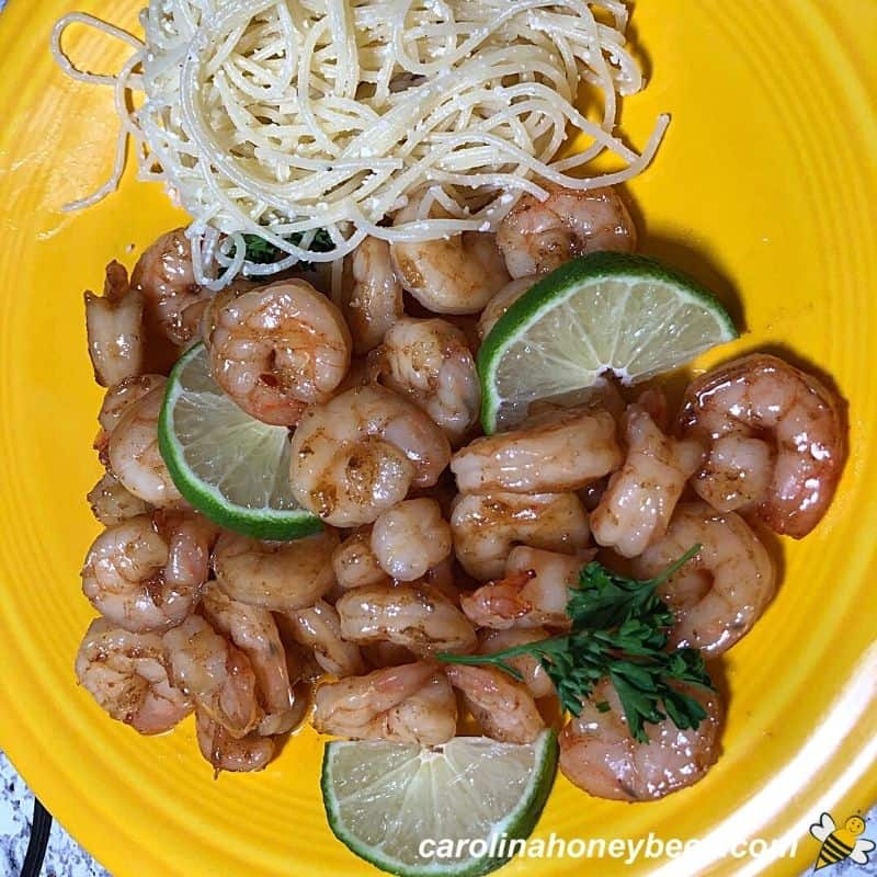 Stir fry honey lime shrimp recipe on a yellow plate with pasta image.