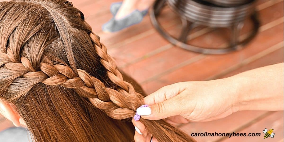 Smoothing flyaways of braided hair with light coat of beeswax image.
